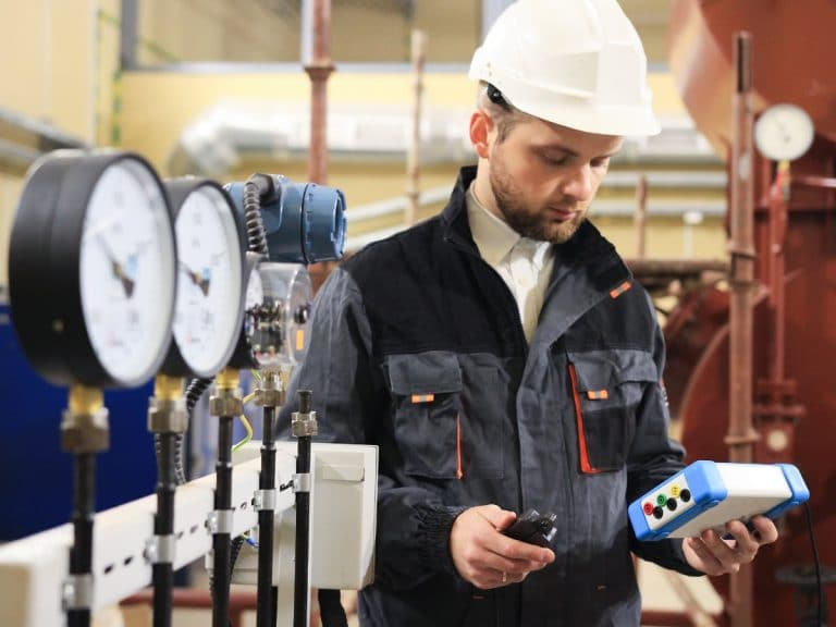 Technician operator measuring value of pressure, temperature and flow on gas and oil processing platform to monitor quality of process.